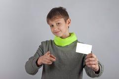 Χαριτωμένος χαμογελώντας έφηβος που κρατά την άσπρη κάρτα και που δείχνει προς σας Στοκ εικόνες με δικαίωμα ελεύθερης χρήσης
