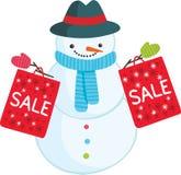 Χαριτωμένος χιονάνθρωπος κινούμενων σχεδίων με τις τσάντες πώλησης Στοκ εικόνα με δικαίωμα ελεύθερης χρήσης
