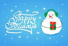 Χαριτωμένος χιονάνθρωπος στα ακουστικά χειμερινών γουνών και ένα δώρο Στοκ φωτογραφία με δικαίωμα ελεύθερης χρήσης