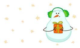 Χαριτωμένος χιονάνθρωπος στα ακουστικά χειμερινών γουνών και ένα δώρο Στοκ Φωτογραφία