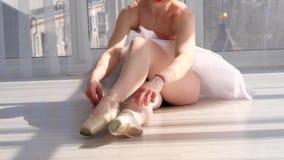Χαριτωμένος χορευτής μπαλέτου στη συνεδρίαση tutu στο πάτωμα και τα δένοντας pointe παπούτσια φιλμ μικρού μήκους