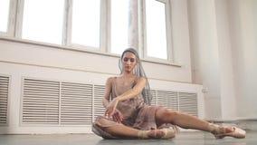 Χαριτωμένος χορευτής μπαλέτου στο γκρίζο φυσικό κοστούμι που αποδίδει στα pointes στο γκρίζο στούντιο απόθεμα βίντεο