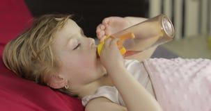 Χαριτωμένος ύπνος κοριτσάκι στο άνετο κρεβάτι στο σπίτι και το χυμό κατανάλωσης από το μπουκάλι απόθεμα βίντεο