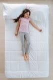 Χαριτωμένος ύπνος μικρών κοριτσιών στο κρεβάτι Στοκ Φωτογραφίες