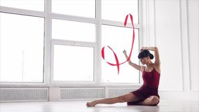 Χαριτωμένος gymnast στρίβει το κώλυμα, καθμένος σε μια αίθουσα χορού απόθεμα βίντεο