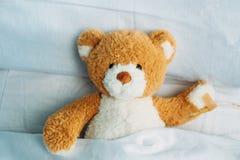 Χαριτωμένος teddy αντέχει το παιχνίδι στο κρεβάτι με το μετρητή πτώσης Στοκ Εικόνες