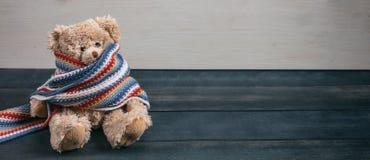 Χαριτωμένος teddy αφορά με τη ζωηρόχρωμη συνεδρίαση μαντίλι το μπλε ξύλινο υπόβαθρο στοκ φωτογραφία με δικαίωμα ελεύθερης χρήσης