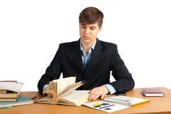 Χαριτωμένο άτομο που διαβάζει ένα βιβλίο στον πίνακα στοκ εικόνα