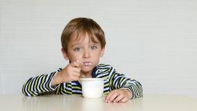 Χαριτωμένο ένα αγόρι κάθεται στον πίνακα και με την όρεξη τρώει το προϊόν ή το γιαούρτι ξινός-γάλακτος Παιδικές τροφές Παραγωγή φ απόθεμα βίντεο