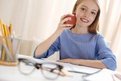 Χαριτωμένο έξυπνο κορίτσι που τρώει ένα μήλο Στοκ Εικόνες