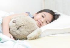 Χαριτωμένο λίγα ασιατικά χαμόγελο και αγκάλιασμα κοριτσιών teddy αντέχουν Στοκ Εικόνες
