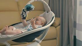 Χαριτωμένο λίγο μωρό με το ομοίωμα λικνίζει από το σύγχρονο λίκνο απόθεμα βίντεο