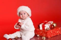 Χαριτωμένο αγοράκι με τις διακοσμήσεις Χριστουγέννων πέρα από το κόκκινο Στοκ Εικόνα