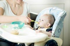Χαριτωμένο αγοράκι 9 μηνών που τρώει από το κουτάλι Στοκ εικόνα με δικαίωμα ελεύθερης χρήσης