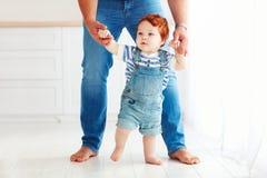 Χαριτωμένο αγοράκι μικρών παιδιών που μαθαίνει να περπατά με τη βοήθεια του πατέρα Στοκ Εικόνες