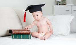 Χαριτωμένο αγοράκι στις πάνες και συνεδρίαση βαθμολόγησης ΚΑΠ στο κρεβάτι με τα βιβλία Στοκ Φωτογραφία