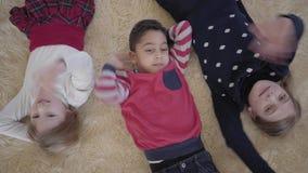 Χαριτωμένο αγόρι αφροαμερικάνων και δύο ξανθά καυκάσια κορίτσια που βρίσκονται στο πάτωμα σε ετοιμότητα τον μπεζ χνουδωτό τάπητα  απόθεμα βίντεο