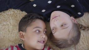 Χαριτωμένο αγόρι αφροαμερικάνων και ξανθό καυκάσιο κορίτσι που βρίσκονται στο πάτωμα στον μπεζ χνουδωτό τάπητα και που εξετάζουν  απόθεμα βίντεο