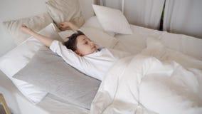 Χαριτωμένο αγόρι εφήβων που ξυπνά το πρωί Τέντωμα αγοριών στο κρεβάτι απόθεμα βίντεο