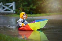 Χαριτωμένο αγόρι με τη ζωηρόχρωμη ομπρέλα ουράνιων τόξων μια βροχερή ημέρα, που έχει το φ Στοκ εικόνα με δικαίωμα ελεύθερης χρήσης