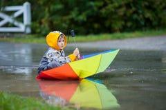 Χαριτωμένο αγόρι με τη ζωηρόχρωμη ομπρέλα ουράνιων τόξων μια βροχερή ημέρα, που έχει το φ Στοκ Φωτογραφία