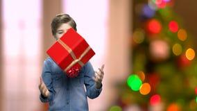 Χαριτωμένο αγόρι με το κιβώτιο δώρων Χριστουγέννων απόθεμα βίντεο