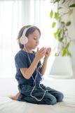 Χαριτωμένο αγόρι με το τηλέφωνο και τα επικεφαλής τηλέφωνα, μουσική ακούσματος Στοκ φωτογραφίες με δικαίωμα ελεύθερης χρήσης