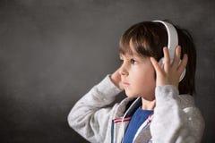 Χαριτωμένο αγόρι με το τηλέφωνο και τα επικεφαλής τηλέφωνα, μουσική ακούσματος Στοκ φωτογραφία με δικαίωμα ελεύθερης χρήσης
