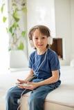 Χαριτωμένο αγόρι με το τηλέφωνο και τα επικεφαλής τηλέφωνα, μουσική ακούσματος Στοκ Φωτογραφίες
