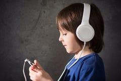 Χαριτωμένο αγόρι με το τηλέφωνο και τα επικεφαλής τηλέφωνα, μουσική ακούσματος Στοκ εικόνες με δικαίωμα ελεύθερης χρήσης