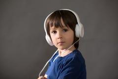 Χαριτωμένο αγόρι με το τηλέφωνο και τα επικεφαλής τηλέφωνα, μουσική ακούσματος Στοκ Φωτογραφία