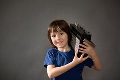 Χαριτωμένο αγόρι με το τηλέφωνο και τα επικεφαλής τηλέφωνα, μουσική ακούσματος Στοκ εικόνα με δικαίωμα ελεύθερης χρήσης