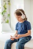 Χαριτωμένο αγόρι με το τηλέφωνο και τα επικεφαλής τηλέφωνα, μουσική ακούσματος Στοκ Εικόνες