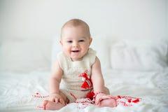 Χαριτωμένο αγόρι μικρών παιδιών μωρών, που παίζει με τα άσπρα και κόκκινα βραχιόλια στοκ φωτογραφία