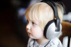 Χαριτωμένο αγόρι μικρών παιδιών που φορά τα μεγάλα ακουστικά που ακούνε τη μουσική Στοκ Εικόνες