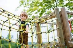 Χαριτωμένο αγόρι παιδιών που έχει τη διασκέδαση με την αναρρίχηση στην παιδική χαρά παιδιών στοκ εικόνες
