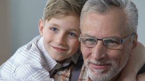 Χαριτωμένο αγόρι που αγκαλιάζει το granddad του, έκφραση αγάπης, οικογενειακή επικοινωνία, υποστήριξη απόθεμα βίντεο