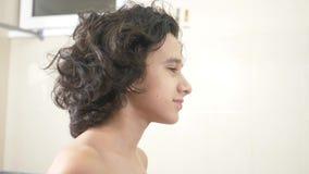 Χαριτωμένο αγόρι που βουρτσίζει τη σγουρή τρίχα του μπροστά από τον καθρέφτη λουτρών 4K απόθεμα βίντεο