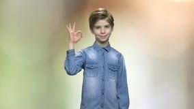 Χαριτωμένο αγόρι που δίνει το ΕΝΤΑΞΕΙ σημάδι απόθεμα βίντεο