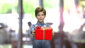 Χαριτωμένο αγόρι που δίνει το κόκκινο κιβώτιο δώρων φιλμ μικρού μήκους