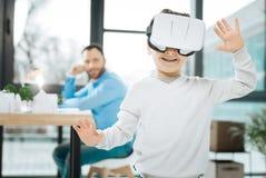 Χαριτωμένο αγόρι που δοκιμάζει την κάσκα VR στην εργασία πατέρων Στοκ φωτογραφίες με δικαίωμα ελεύθερης χρήσης