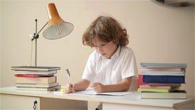 Χαριτωμένο αγόρι που κάνει την εργασία Η εκπαίδευση παιδιών, σπουδαστής γράφει σε ένα σημειωματάριο απόθεμα βίντεο