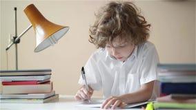 Χαριτωμένο αγόρι που κάνει την εργασία Η εκπαίδευση παιδιών, σπουδαστής γράφει σε ένα σημειωματάριο φιλμ μικρού μήκους