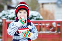 Χαριτωμένο αγόρι που κρατά το μεγάλο φλυτζάνι και το ζεστά ποτό και το marshmallo σοκολάτας Στοκ φωτογραφίες με δικαίωμα ελεύθερης χρήσης