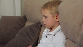 Χαριτωμένο αγόρι που παίζει τα τηλεοπτικά παιχνίδια στο σπίτι Υψηλή ανάλυση φιλμ μικρού μήκους