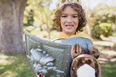 Χαριτωμένο αγόρι που στέκεται και που προσποιείται να είναι ιππότης Στοκ εικόνες με δικαίωμα ελεύθερης χρήσης