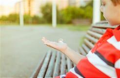 Χαριτωμένο αγόρι που φαίνεται φυσαλίδα σαπουνιών στο ανοικτό χέρι του Στοκ εικόνες με δικαίωμα ελεύθερης χρήσης