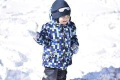 Χαριτωμένο αγόρι που φορά τα θερμά ενδύματα που παίζουν στο χειμερινό δάσος στο beauti στοκ φωτογραφία