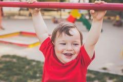 Χαριτωμένο αγόρι που χαμογελά και που παίζει στην παιδική χαρά στοκ εικόνα