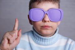 Χαριτωμένο αγόρι στα ιώδη γυαλιά ηλίου με τους αδιαφανείς φακούς που δείχνει πρός τα πάνω στοκ εικόνες με δικαίωμα ελεύθερης χρήσης